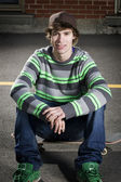 Young skateboarder sitting on his board — Stock Photo