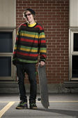 若いスケートボーダー彼のボードを持って立っています。 — ストック写真