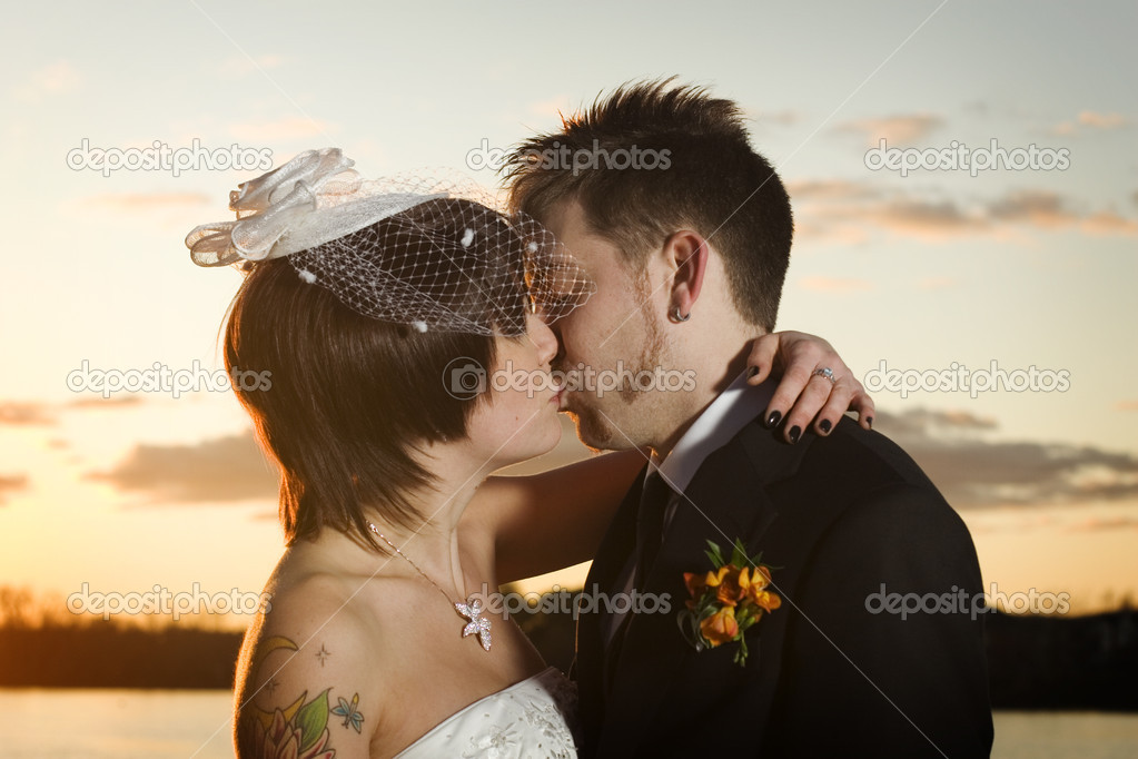 Young newlyweds kissing along riverbank at sunset — Stock Photo #5852347
