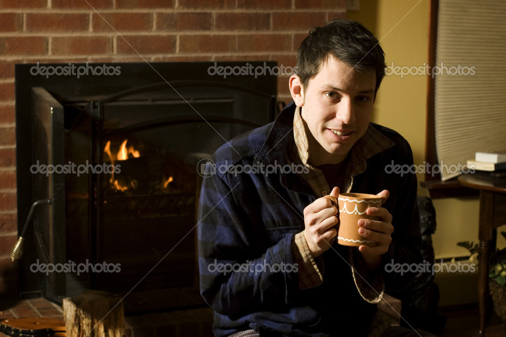Young man warming up by fire after playing outside all day in the snow — Stock Photo #5852526