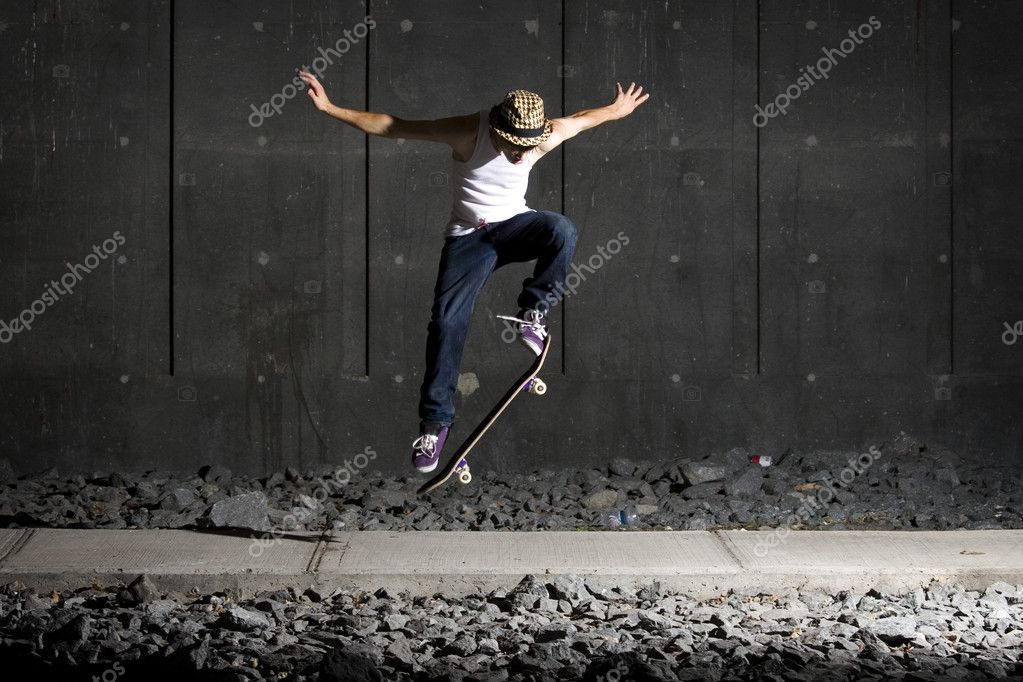 Skateboarder doing an ollie on walking path with concrete wall behind — Stock Photo #5853232