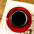Black coffee, red enamel mug, two old silver spoons on embroider — Stock Photo #5611614