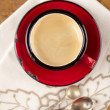 Espresso coffee in red enamel mug, two old silver spoons, embroi — Stock Photo #5611625