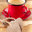 Photo: Espresso coffee, red enamel mug, two wooden hearts and festive