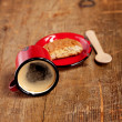 Overturned espresso coffee in red enamel mug with saucer, woode - Stock Photo