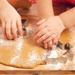 Little girls cutting christmas gingerbread cookies, hands only — Stock Photo #5612154