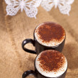 Hot frothy drink cappuccino chokolate dusted, white paper butter — Stock Photo