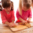 Two busy little girls kneading and rolling gingerbread dough — Stock Photo #5612251
