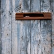 Stock Photo: Very old postbox in wheathered wooden fence