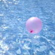 Air baloon floating on blue glittering water - Stock Photo