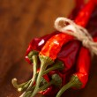 Red hot chillies pepper bunch in wooden bowl background — Stock Photo #5617776