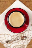 Espresso coffee in red enamel mug, two old silver spoons, embroi — Stock Photo