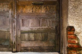 Very old wooden door and rundown brick wall, fragment — Stock Photo