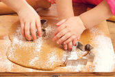Little girls cutting christmas gingerbread cookies, hands only — Stock Photo