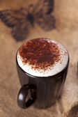 Hot frothy drink cappuccino chokolate dusted, black paper butter — Stock Photo