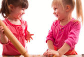 Two little girls with rolling pins baking cookies — Stock Photo
