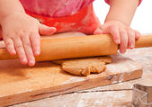 Little girl rolling a gingerbread dough, hands only, — Stock Photo