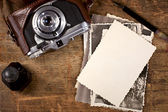Vintage ink and pen, old photos and camera on old wooden table — Stock Photo