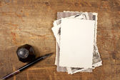 Vintage ink pen, inkpot and old photographs on wooden table — Stock Photo