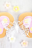 Ornate paper batterfly and ginger cookies with sugar flowers — Stock Photo