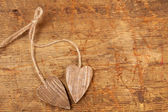 Tied wooned hearts on old wood — Stock Photo