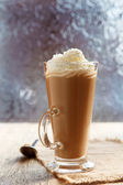 Coffee latte macchiato with cream in glass near window — Stock Photo
