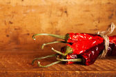 Hot red chillies paper bunch inside wooden case — Stock Photo