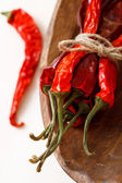 Red hot chillies pepper bunch in wooden bow — Stock Photo