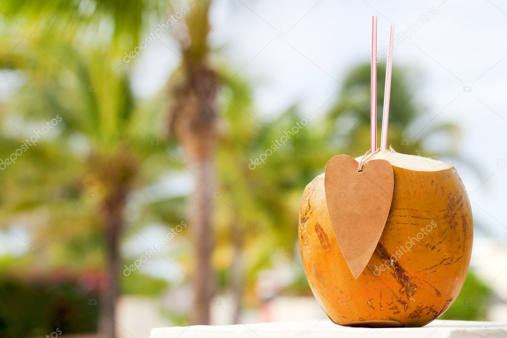 Drinking coconut cocktail with paper heart and straws, shallow dof — Stock Photo #5612614