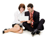 Young man and woman sitting on the floor, looking at laptop. — Stock Photo