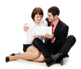 Young man and woman sitting on the floor and look into the noteb — Stock Photo