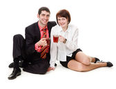 Young, smiling, woman and man sitting on the floor, drinking tea — Stock Photo