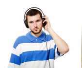 A young guy with a beard, listening to music on headphones. — Stock Photo