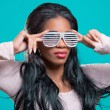 Beautiful young woman wearing fancy sunglasses, isolated on blue — Stock Photo #5621309