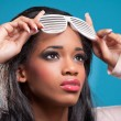 Stock Photo: Beautiful young woman wearing fancy sunglasses, isolated on blue