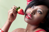 Beautiful young black woman eating a strawberry — Stock Photo