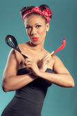 Beautiful happy pin-up style housewife with kitchen utensils — Stock Photo