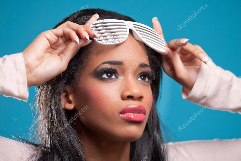 Portrait of beautiful young woman wearing fancy sunglasses, isolated on blue — Stock Photo #5621314