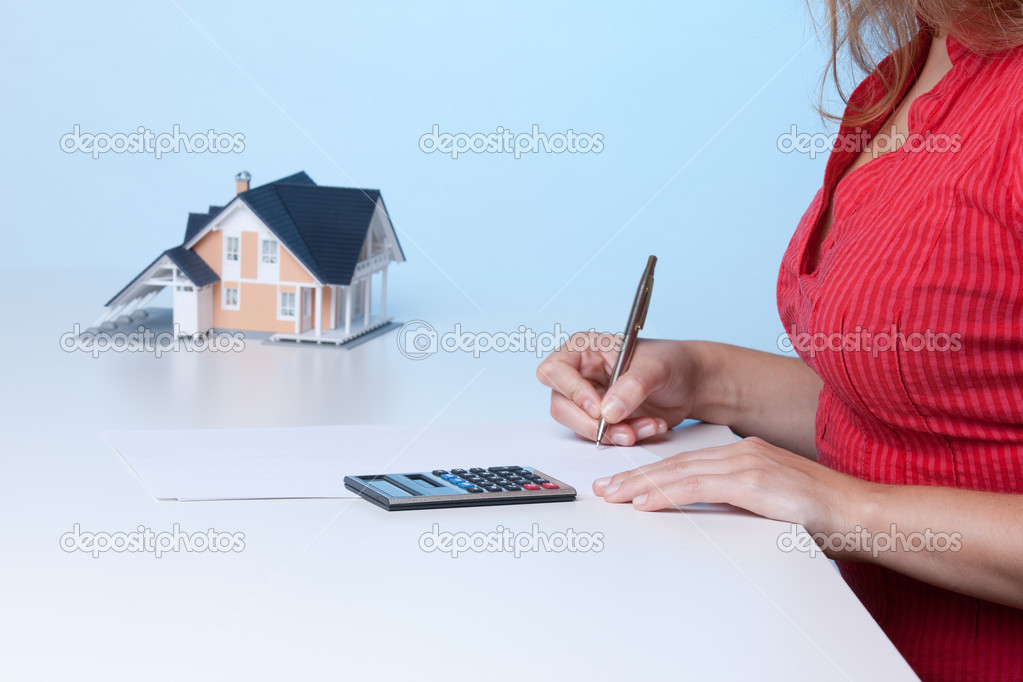 Real estate broker calculating amount of payments family house mortgage. Focused on calculator. — Lizenzfreies Foto #6560479