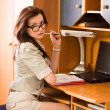 Stock Photo: Businesswomsitting at desk doing paperwork
