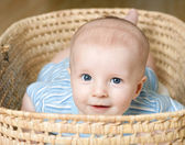 Little boy lying in wicker basket — Stock Photo