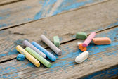 Coloured pieces of chalk on the board — Stock Photo