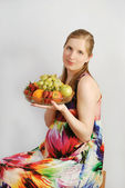 The pregnant young woman with a dish of fruit — Stock Photo
