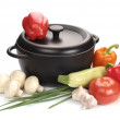 Black cast-iron cauldron with vegetables - Stock Photo