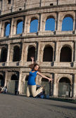 Happy young woman jumping against coliseum in Rome — Stock Photo