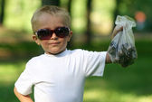 The little boy in dark glasses with a package of pines — Stock Photo