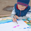 Stock Photo: Little boy painting outdoors