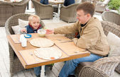 Little boy and his father eating soup in summer cafe — Stock Photo