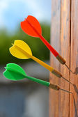 Three darts at wooden board. — Stock Photo