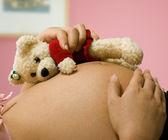 怀孕的母亲抱着一个玩具熊 — 图库照片